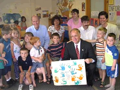 Governor Douglas receives hand-made poster from Oak Hill Childcare Center
